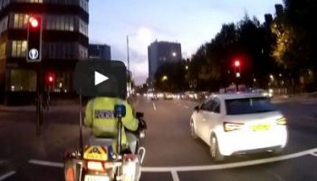 Video: Driver jumps red light next to police bike