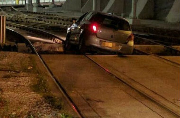 Oblivious motorist drives on tram tracks and gets stuck at station