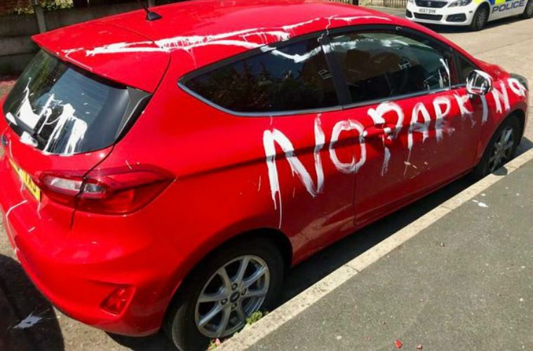 """""""No parking"""" painted on cars parked in residential street near airport"""
