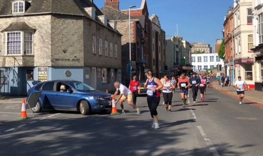 Watch: Arrogant motorist drives through half marathon runners
