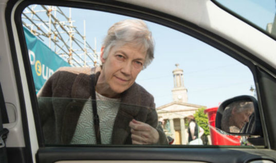 Climate change activist takes to knocking on windows asking drivers to switch off engines