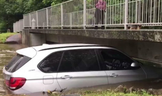 Video: £60k BMW X5 swept away by flood and left wedged under bridge