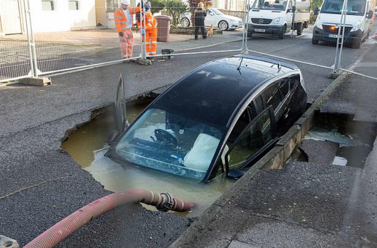 Motorist drives into huge sinkhole