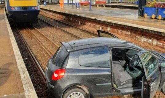 Car lands on rail lines in the Highlands